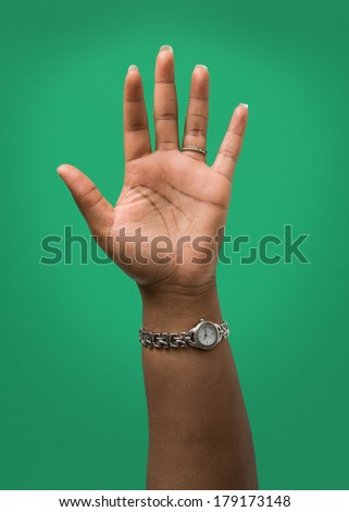 Raised Female Hand Wearing Wedding Ring and Watch Isolated on Green - stock photo