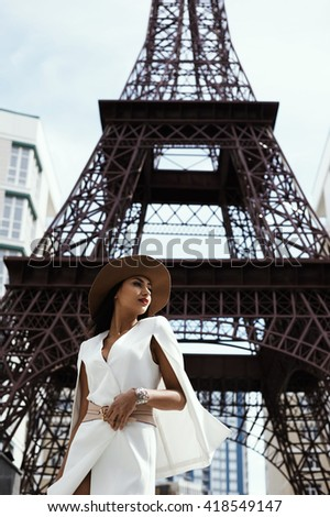raven haired indian lady posing against fake Eiffel Tower