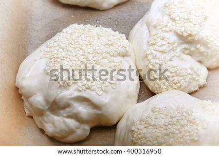 raw bread buns with sesame seeds from  dough home baking
