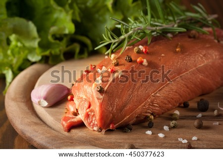 Raw fresh beef meat full steak with rosemary, pepper, tomatoes, garlic, salad and salt on wooden background