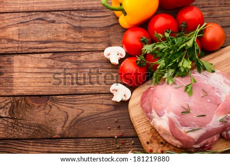 Raw meat for barbecue with fresh vegetables and mushroom on wooden surface, menu cooking recipes. Food, raw steak, beef steak bbq, tomatoes, peppers, spices for cooking meat. Free space for text.  - stock photo
