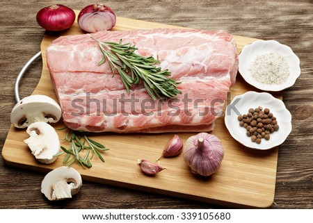 Raw meat for barbecue with fresh vegetables and mushrooms on wooden surface - stock photo