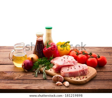 Raw meat for barbecue with fresh vegetables on wooden surface. Food, meat raw steak, beef steak bbq, tomatoes, peppers, spices for cooking meat. Free space for text.  - stock photo
