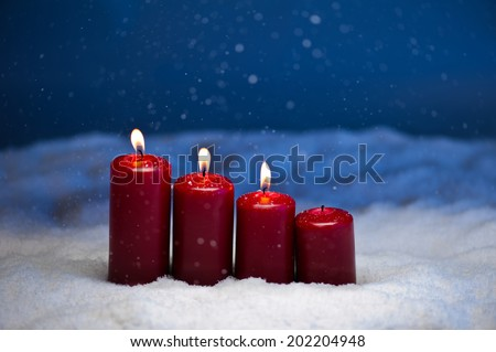 3rd Advent candles in snow and snowfall - stock photo