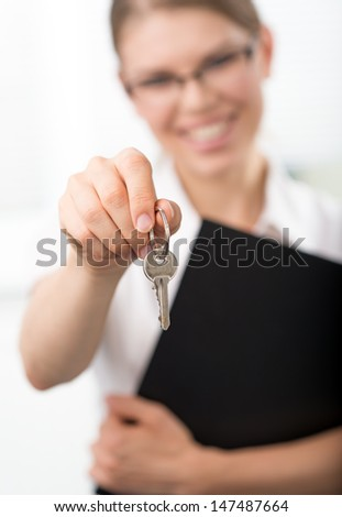 Real estate agent holding illustrated house in her hands. Young smiling female mortgage consultant.   - stock photo