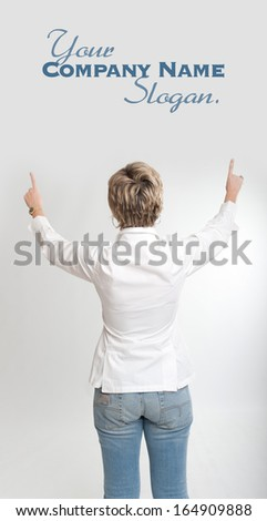 Rear view of a woman pointing at something with both hands  - stock photo