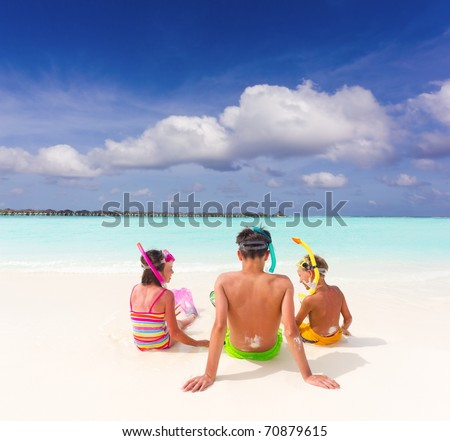 Rear view of three young children with snorkels sat on beach, turquoise sea, blue sky and cloudscape background.