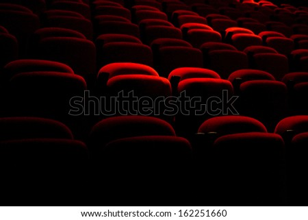 Red back seat in a dark movie theater