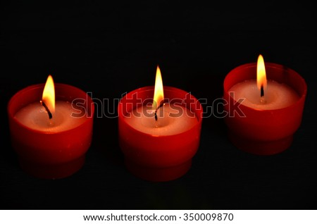 red candles with christmas ligts on Christmas tree and tangerines in atmospheric light