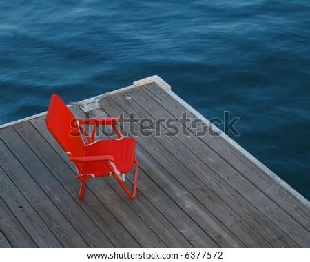 Red chair on dock, boston harbor massachusetts - stock photo