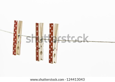 3 red clothespin on a clothesline on white background