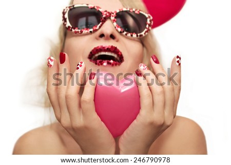 Red pink manicure and makeup with hearts on the blonde girl with glasses. - stock photo