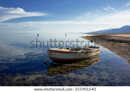 Red Sea in a calm weather. Bedouin women on the reef. Dahab. Egypt.                         - stock photo