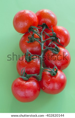 Red tomatoes with green leaves. Top view. Green background