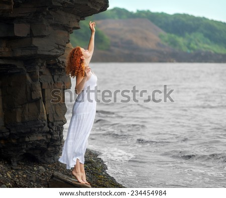 Redhead woman in white dress standing on beach and looking to somewhere. Soft focus. - stock photo