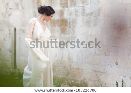 ??Refined woman'profile  with  elegant pose looking down with a mysterious smile on her beautiful face.  - stock photo