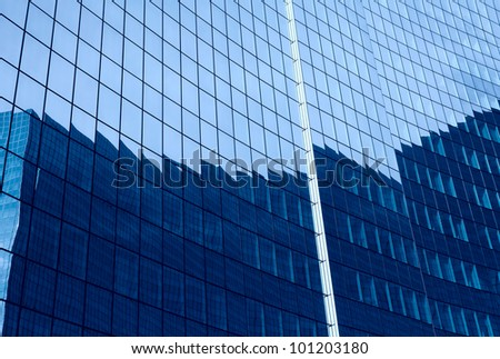Reflection in glass wall of business building in another - stock photo