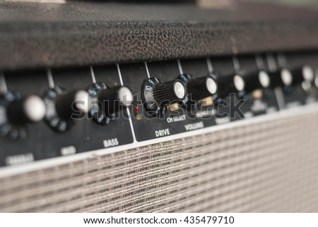 Retro guitar amplifier.Closeup of controls and front cover of retro guitar amplifier, loudspeaker. - stock photo