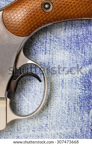 revolver on blue jeans background, close-up, part of - stock photo