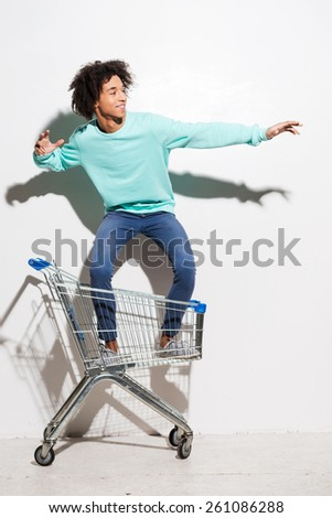 Riding a shopping cart. Playful young African man riding in shopping cart against grey background  - stock photo