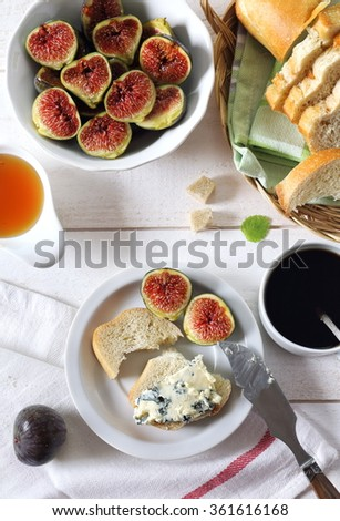Ripe figs, blue cheese, honey, baguette and cup of coffee - stock photo