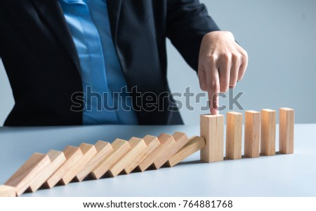 Risk management Businesswoman stop domino effect. leadership has solution for problem.