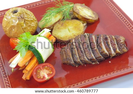 roast  fillet duck with potatoes on red plate