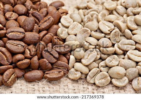 Roasted and  not roasted coffee beans on the sacking. Small DOF.