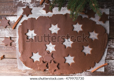 Roll out the dough to cut out stars on a wooden background