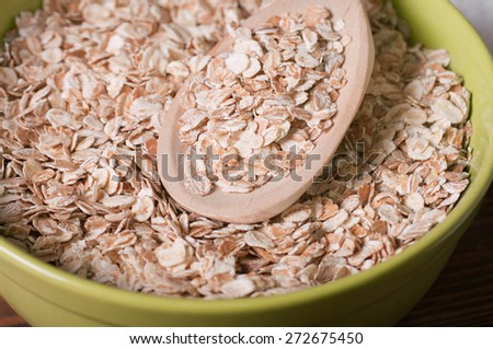 rolled oats heaped in a glass bowl - stock photo