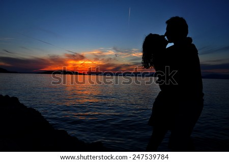 Romantic couple silhouette over sea sunset background - stock photo