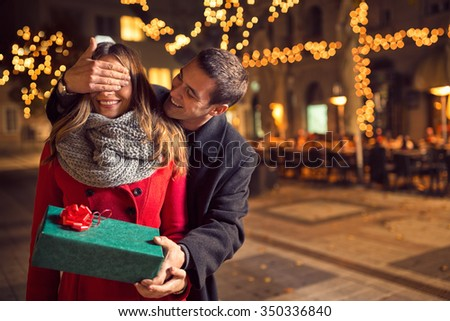 romantic surprise for Christmas, woman  receives a gift from her boyfriend - stock photo