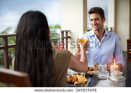 romantic young couple at table toasting, dinner on the balcony - stock photo