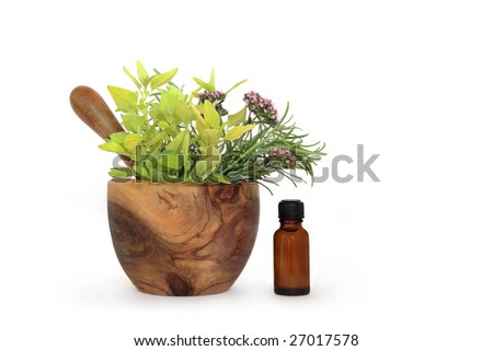 Rosemary, oregano and marjoram herb leaves and flowers in an olive wood mortar with pestle and  aromatherapy essential oil bottle, over white background. - stock photo