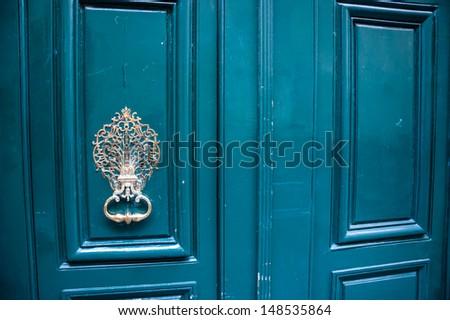 Royal style doorknocker on turquoise door. - stock photo