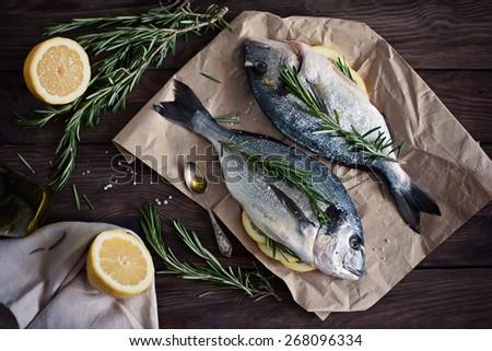 ?rude Dorado fish with lemon and rosemary on the table - stock photo