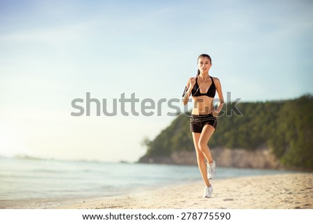 Runner athlete running on sand coast, woman fitness jogging workout wellness concept. - stock photo