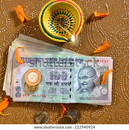 100 rupee bank notes and coins with indian traditional lamp. Bird eye view. - stock photo