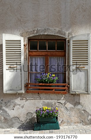 rustic window with old wood shutters and flower pots in stone rural house, Switzerland. - stock photo