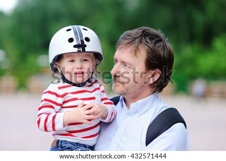 ?rying toddler boy in safety helmet and his middle age father outdoors - stock photo
