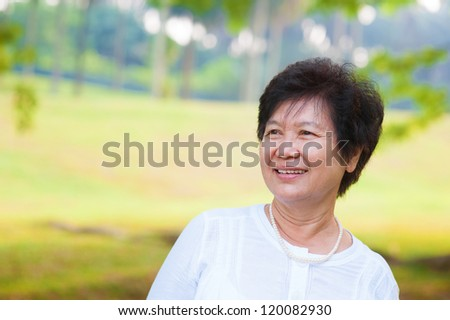 60's Asian senior woman at park in a morning - stock photo