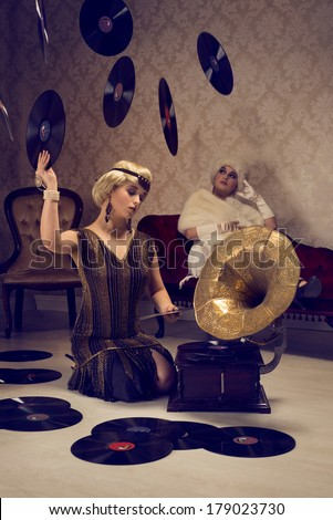 20s elegant women at a party choosing music - stock photo