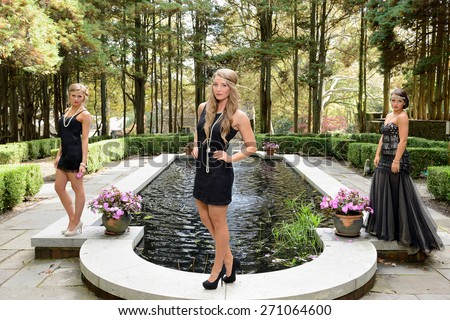 1920's fashion shoot - Beautiful young Caucasian women wearing a black vintage appearing dresses and headbands - standing in garden and in front of fountain - friends - stock photo