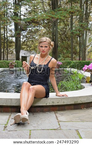 1920's fashion shoot -  Stunning young model seated in garden garden courtyard in front of small pond - holding pearl necklace out while looking at viewer