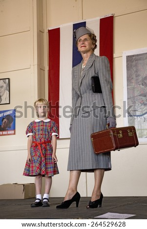 1940s fashion show reenactment in front of World War II flag and woman holding suitcase & young girl at Mid-Atlantic Air Museum World War II Weekend and Reenactment in Reading, PA held June 18, 2008 - stock photo