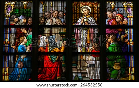 'S HERTOGENBOSCH, THE NETHERLANDS - JULY 23, 2011: Stained Glass Window depicting a saint performing the sacrament of Holy Communion in Den Bosch Cathedral, North Brabant. - stock photo
