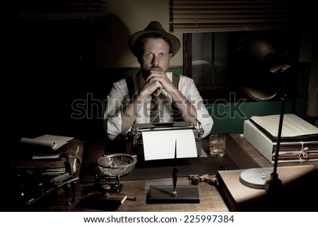 1950s journalist working late at night in his office typing on a typewriter. - stock photo