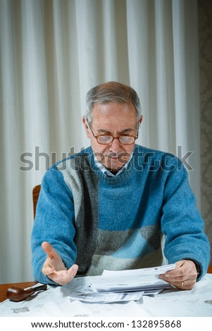 70's Old man worried for the bill - stock photo
