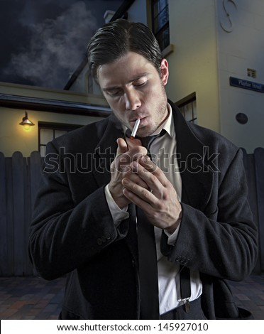 1940's style gangster lights a cigarette - stock photo