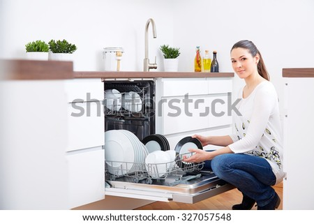 20s woman in kitchen, empty out the full dishwasher - stock photo